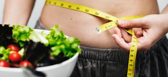 slim woman measuring waist and holding bowl of salad