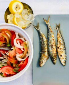Grilled sardines, lemon slices and salad