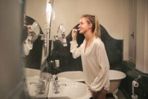 Young woman brushing teeth at bathroom mirror